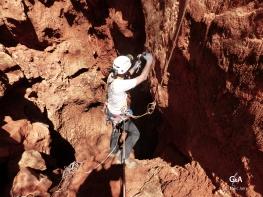 Botswana, gouffre de Waxhu North. Une fois atteint la base de l'entonnoir de sable, il faut, à la main, planter des spits pour assurer la descente de l'équipe (c) M. Jarry.